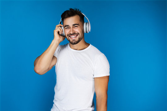 Cute european man smiles and listens something in the headphones