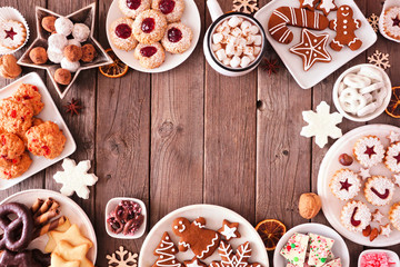 Wall Mural - Christmas table scene of mixed sweets and cookies. Above view over a rustic wood background. Holiday baking concept.
