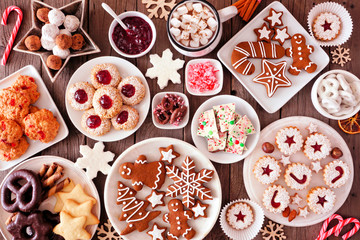 Christmas table scene of assorted sweets and cookies. Top view over a rustic wood background. Holiday baking concept. Fototapete