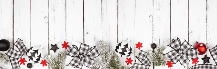 Christmas banner of black and white checked buffalo plaid ribbon, gifts and ornaments. Above view...