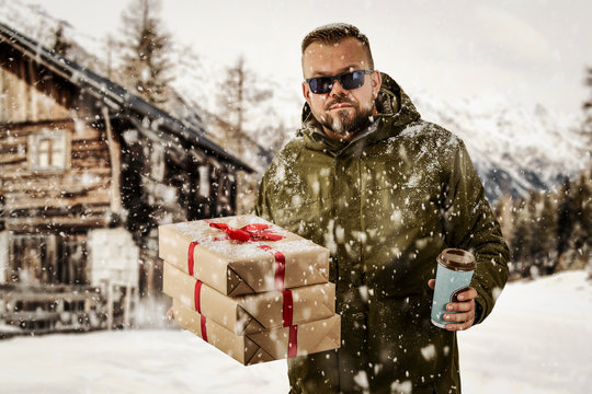 New Year Christmas snowy winter concept Hipster in green coat and hood.Big man with long beard. Xmas party celebration. New year guy with gift boxes and red ribbon tied in bow.Winter holiday, vacation