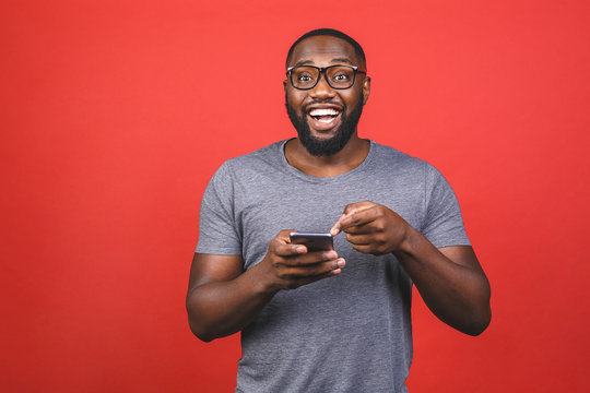 Portrait of handsome excited cheerful joyful delightful african american guy wearing casual sending and getting messages to his lover isolated against red background. Using phone.