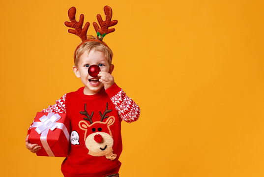 happy funny child boy in red Christmas reindeer costume with gift on yellow   background