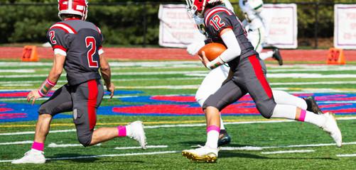 High school football player running with the ball following his blocker