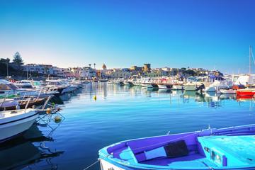 Ischia island and boats in Forio marina. Campania, Italy.