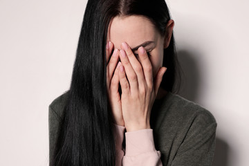 Upset young woman crying against light background