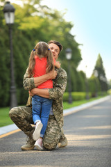 Father in military uniform hugging his little daughter at sunny park
