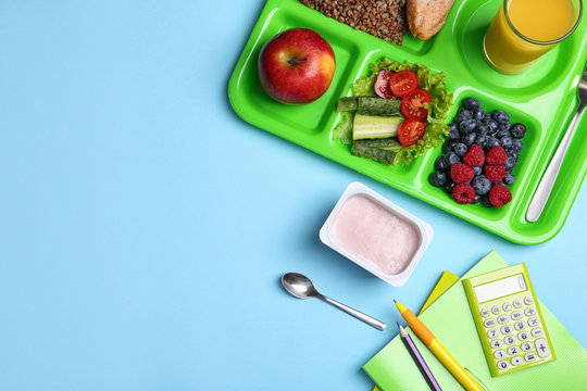 Serving tray of healthy food and stationery on light blue table, flat lay with space for text. School lunch