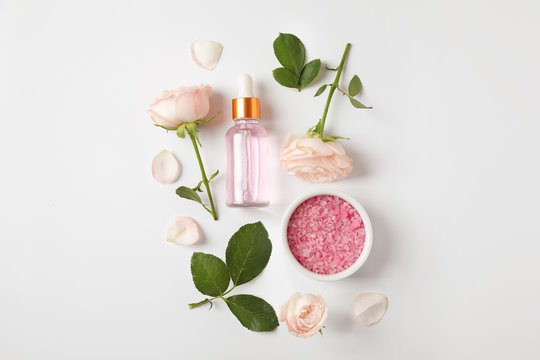 Composition with rose essential oil on white background, top view