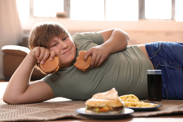 Overweight boy with fast food at home