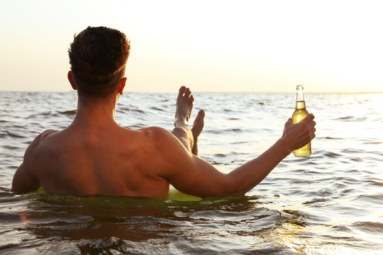Young man with drink on inflatable ring in sea, back view
