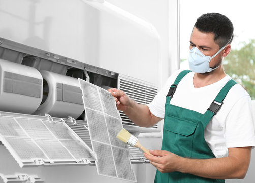 Professional male technician cleaning air conditioner indoors. Repair and maintenance
