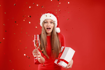 Emotional young woman in Santa hat with Christmas gift and glass of champagne on red background Wall mural