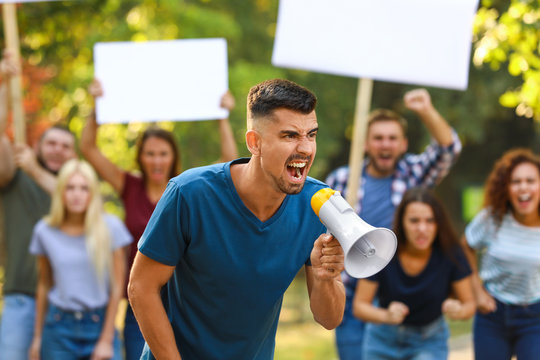 Angry young man with megaphone at protest outdoors