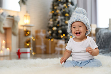 Little baby wearing knitted hat on floor at home. First Christmas