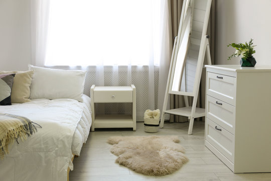 Bedroom interior with modern chest of drawers and mirror