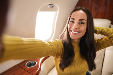 Young woman taking selfie on plane. Comfortable flight