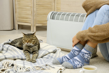 Young woman and cute tabby cat near electric heater at home, closeup