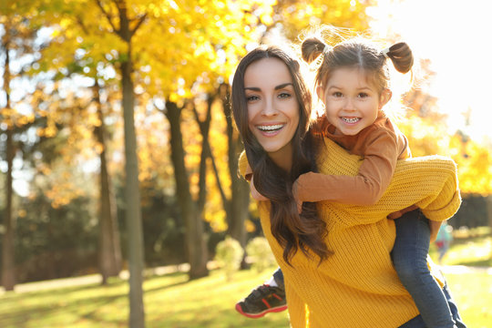 Happy woman with little daughter in sunny park. Autumn walk