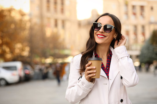 Beautiful woman with cup of coffee on city street. Autumn walk