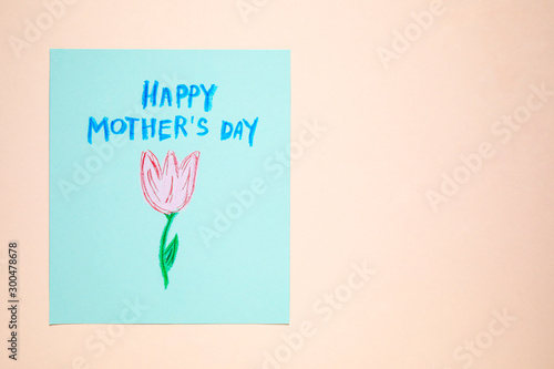 Handmade greeting card for Mother's Day on beige background, top view