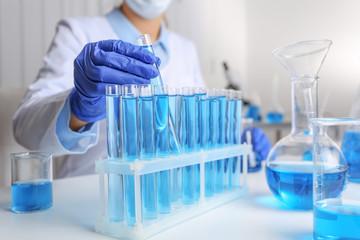Fototapete - Doctor taking test tube with blue liquid, closeup. Laboratory analysis