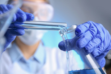 Fototapete - Doctor pouring blue liquid into flask, closeup. Laboratory analysis