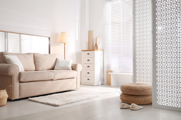 Stylish room interior with white folding screen and sofa