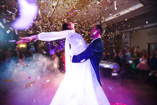 First wedding dance of newlywed. Happy bride and groom and their first dance in the elegant restaurant with a wonderful light with confetti and colorful lights on the background. Wedding day. Together