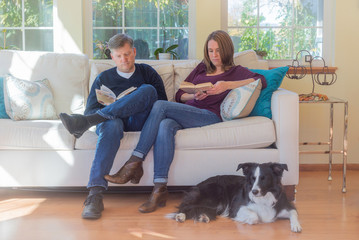 A young couple sit in their sunny living room sharing readng time as their border collie sits on the floor in front of them.