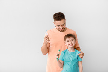 Fotomurales - Portrait of man and his little son brushing teeth on light background