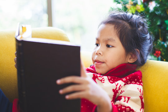 Cute asian child girl reading a book in Christmas celebration