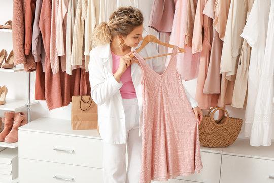 Young woman choosing dress in store