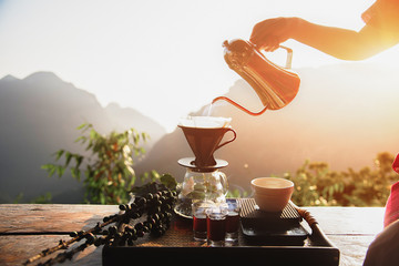 Drip brewing, filtered coffee, or pour-over is a method which involves pouring water over roasted, ground coffee beans contained in a filter. Breakfast concept. - Image