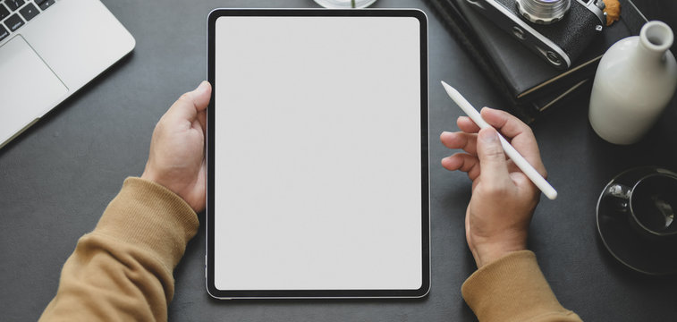 Close-up view of man using blank screen tablet while working in dark modern workplace