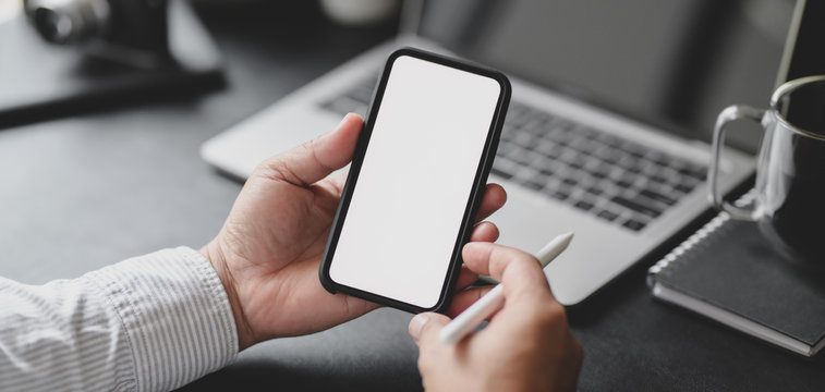 Cropped shot of professional businessman holding blank screen smartphone in dark modern office
