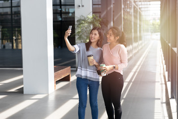 Cheerful young Asian woman in casual clothes two people selfie with smartphone and drinking take away coffee in paper cup in modern office. Technology and lifestyle concept.