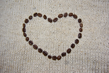 coffee beans heart on the beige background close-up