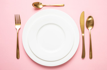 Gold cutlery and dishes set against pink background, formal place setting