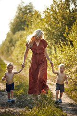 Cheerful mother walking with her two adorable twin-sons