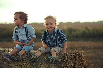 Fond de hotte en verre imprimé Artiste KB Portrait of cheerful children sitting on a sheaf