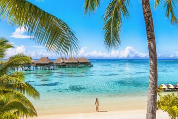 Luxury Tahiti beach resort travel tourist walking on Polynesian beach ocean water at overwater...