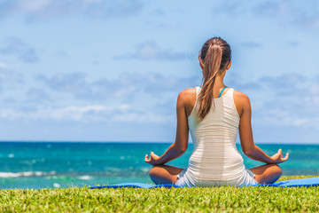 Yoga meditation woman meditating in lotus pose on exercise mat on beach grass.