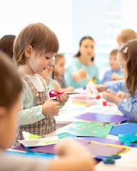 Group of preschool children cutting scissors out paper in kindergarten or daycare
