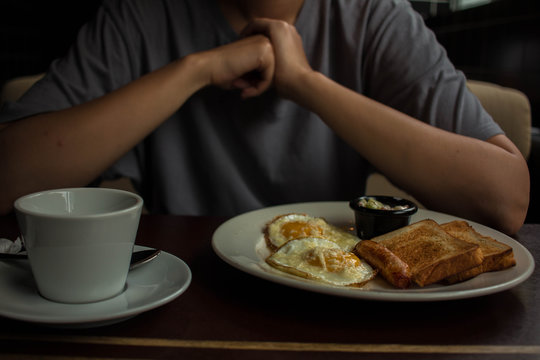 girl in gray t shirt eats scrambled eggs with toast sausage and cheese