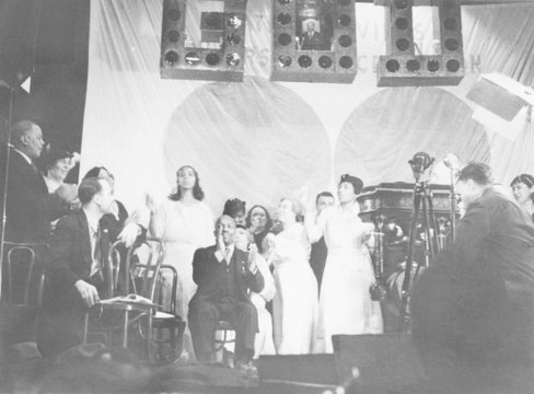 Father Divine leading the singing at one of his meetings. On stage with him are women in white, his