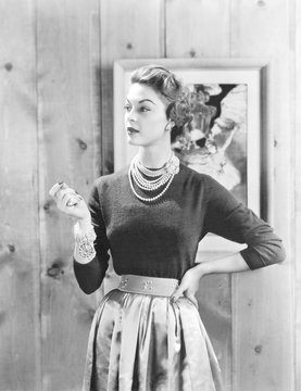 Black cashmere pullover is worn with a satin gathered full skirt and wide belt emphasizing the narrow waist.Dior's new look dominated women's wear for several years after it introduction in 1947. Oct. 1953