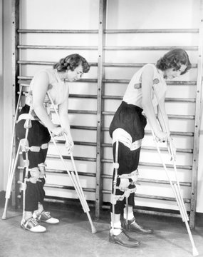 Two adult women polio victims with leg braces adjust their crutches