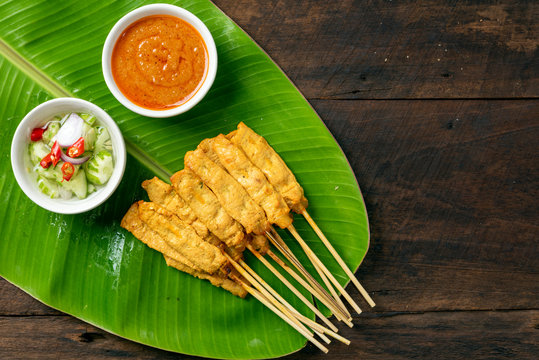 Pork satay - Grilled pork served with peanut sauce or sweet and sour sauce on Banana leaf - Asian food style on wood table