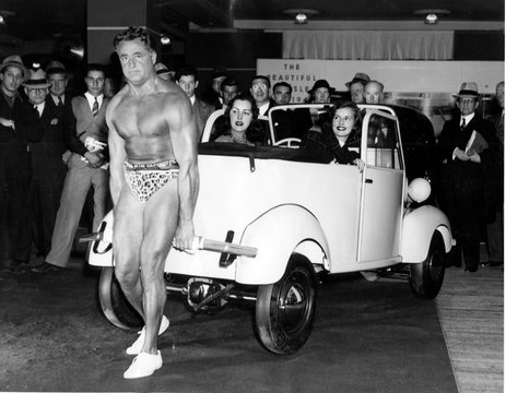 Charles Atlas- The world's strongest man in a muscle-bulging exhibition at The New York Automobile